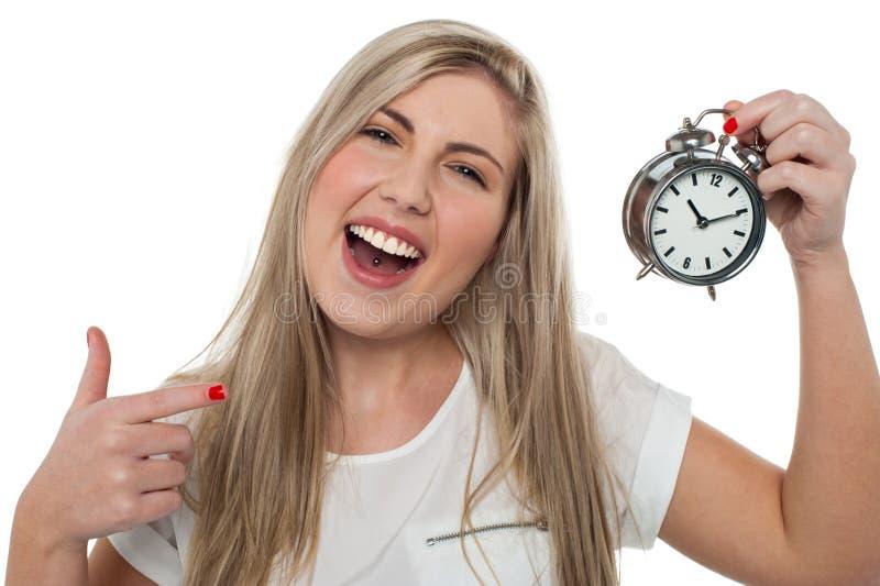 拿着古板的闹钟的兴奋女孩 库存图片