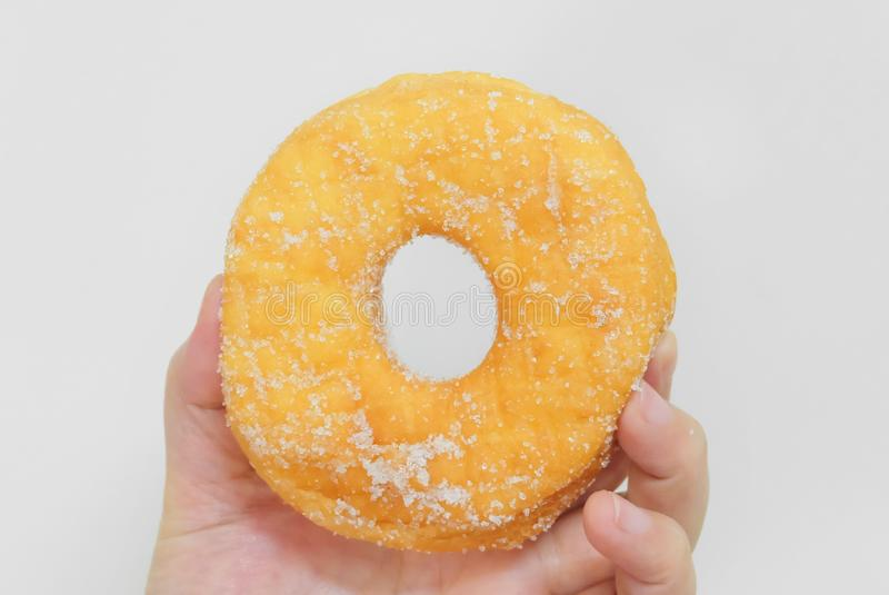 拿着可口上釉圆环用糖的手 免版税库存照片