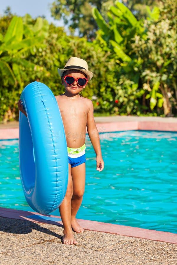 拿着可膨胀的圆环的帽子的逗人喜爱的小男孩 库存图片