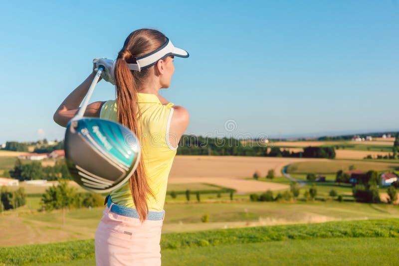 拿着司机俱乐部的少妇在高尔夫球摇摆期间在开始 图库摄影