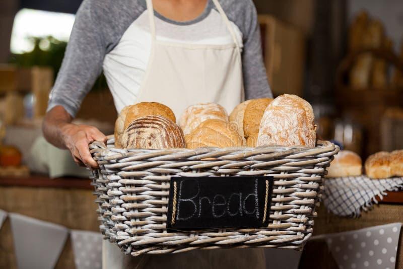 拿着各种各样的面包的柳条筐女职工在柜台在面包店商店 免版税库存照片