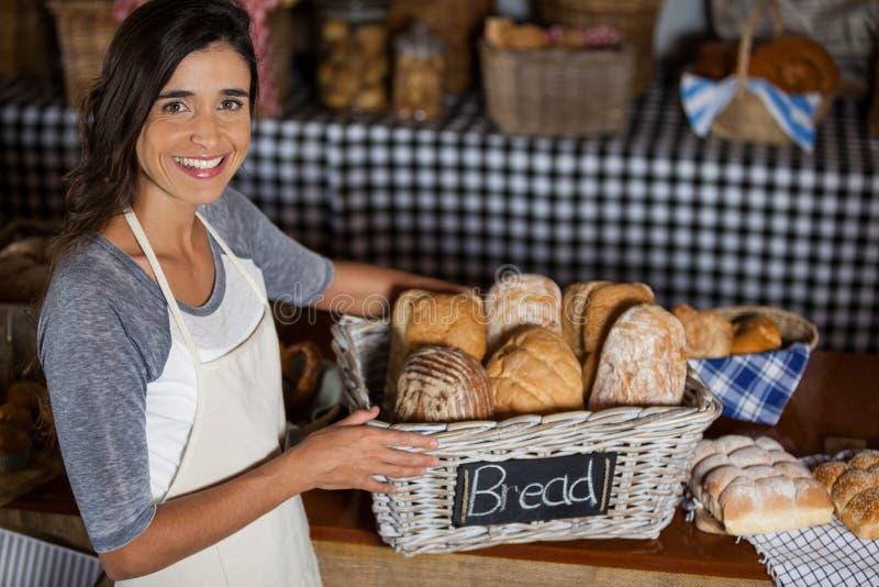 拿着各种各样的面包的柳条筐女职工在柜台在面包店商店 图库摄影