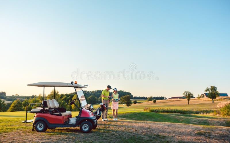 拿着各种各样的高尔夫俱乐部的妇女和她的伙伴或者辅导员在高尔夫车附近 库存照片