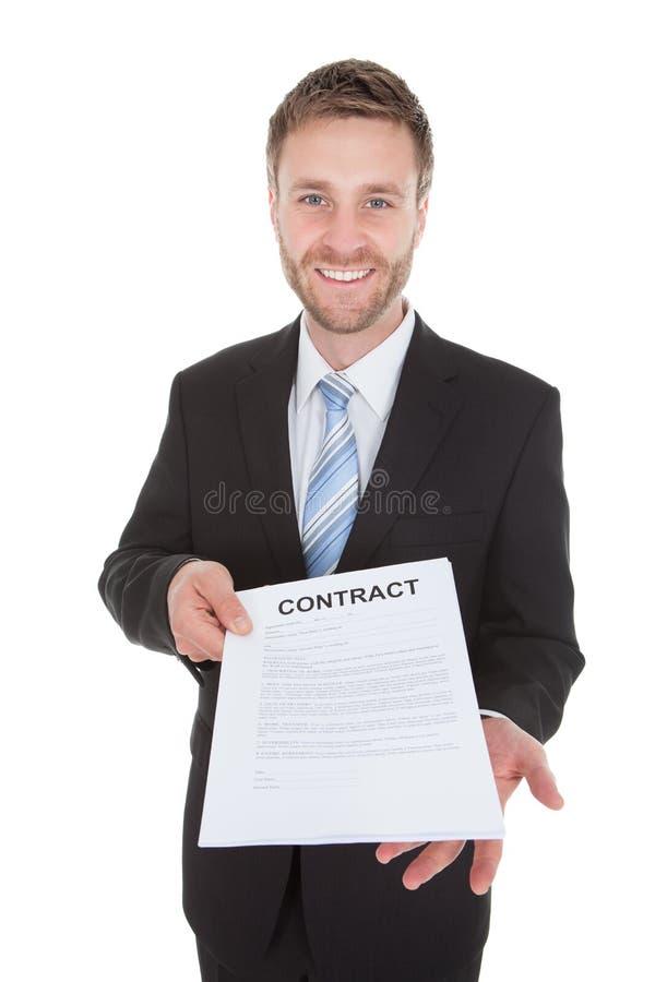 拿着合同纸的确信的商人 免版税库存图片