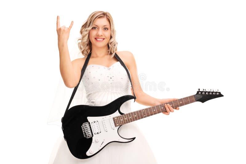 拿着吉他和做岩石姿态的新娘 免版税库存图片