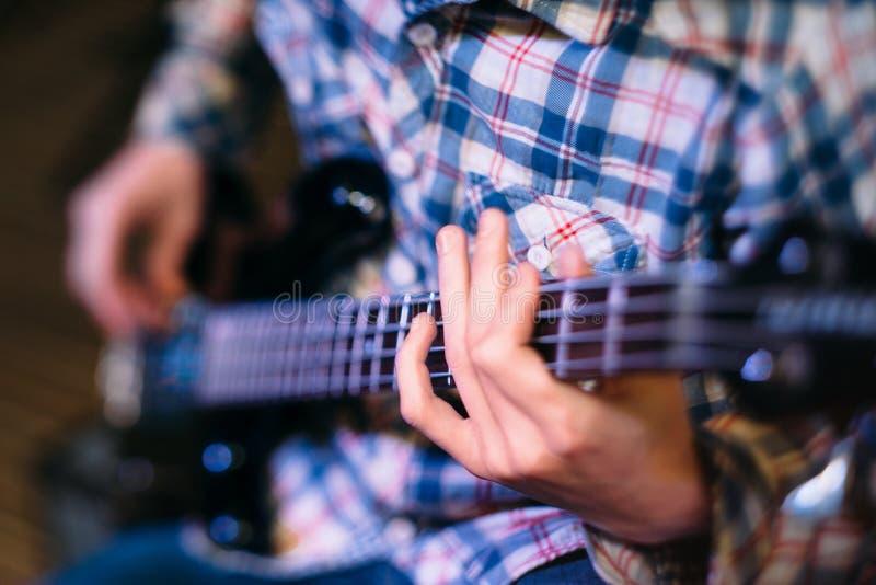 拿着吉他脖子焦点的低音演奏员 免版税库存图片