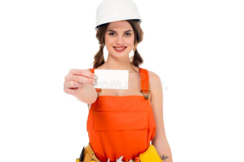 拿着名片的制服和安全帽的微笑的女工, 库存照片