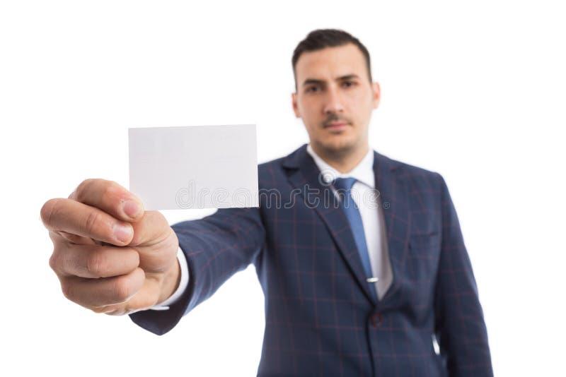 拿着向前白色卡片的年轻英俊的推销员 库存图片