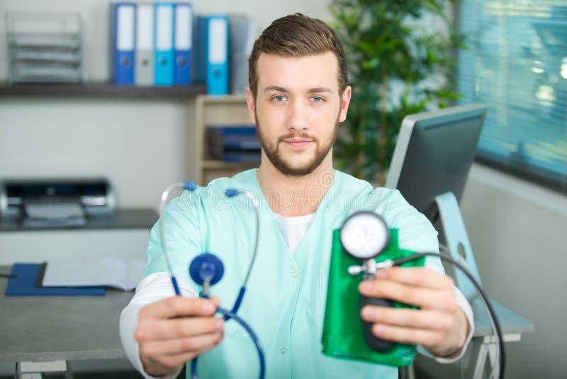 拿着听诊器的年轻男性医生手中 库存图片