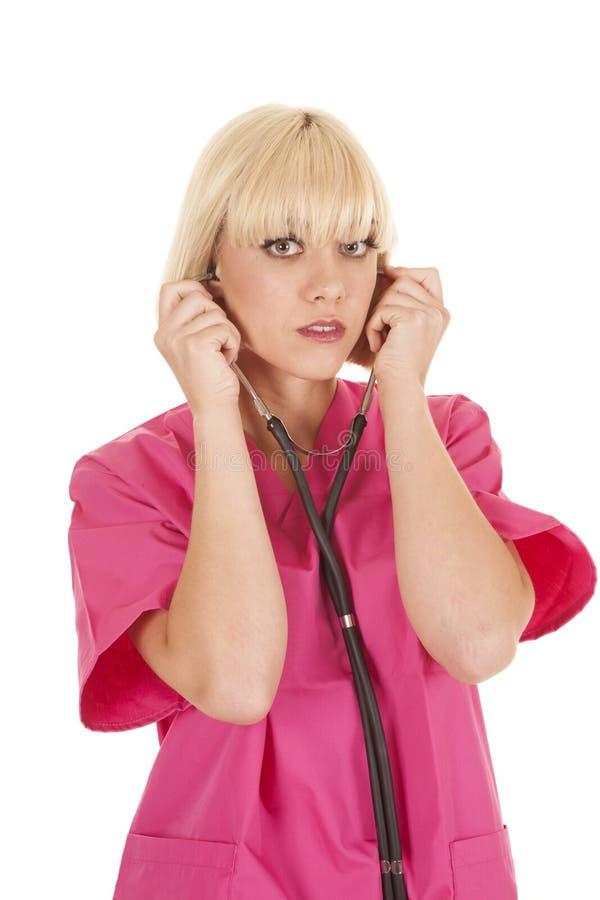 拿着听诊器的护士通过耳朵看 库存照片