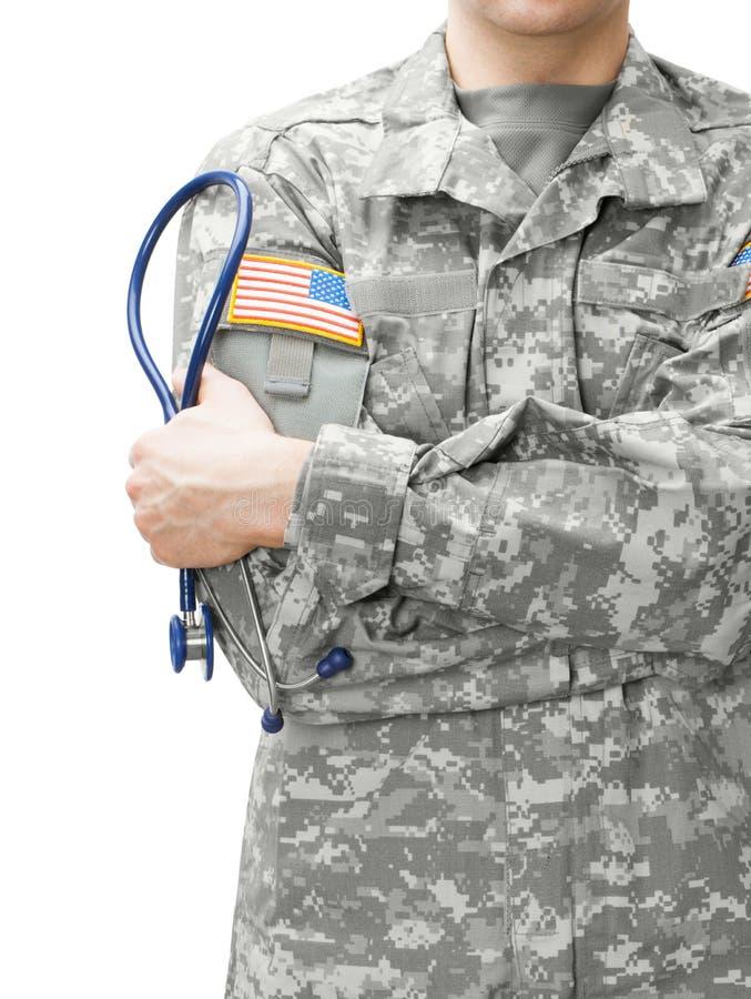 拿着听诊器的美国陆军医生在他的肩膀旁边 图库摄影