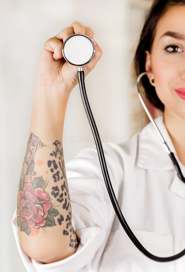 拿着听诊器的胸口零件美丽的被刺字的年轻医生在她的手上,在办公室背景中 库存图片