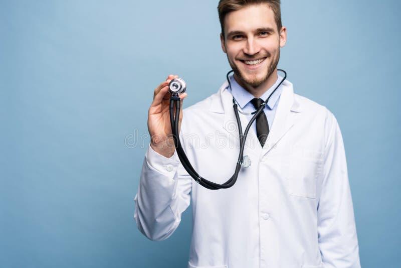 拿着听诊器的英俊的年轻军医,被隔绝在浅兰 库存图片