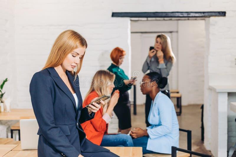 拿着和使用智能手机的妇女在她的手上反对办公室背景 库存照片