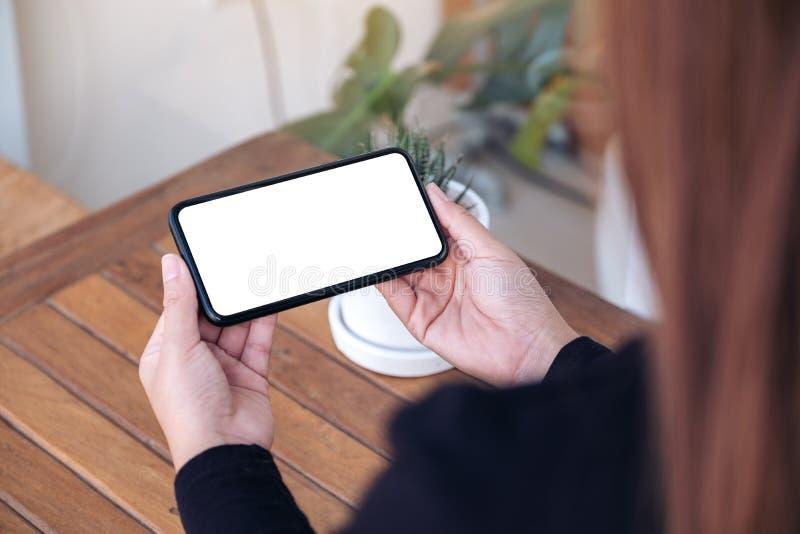 拿着和使用有水平黑屏的妇女一个黑手机为观看在户外 免版税图库摄影