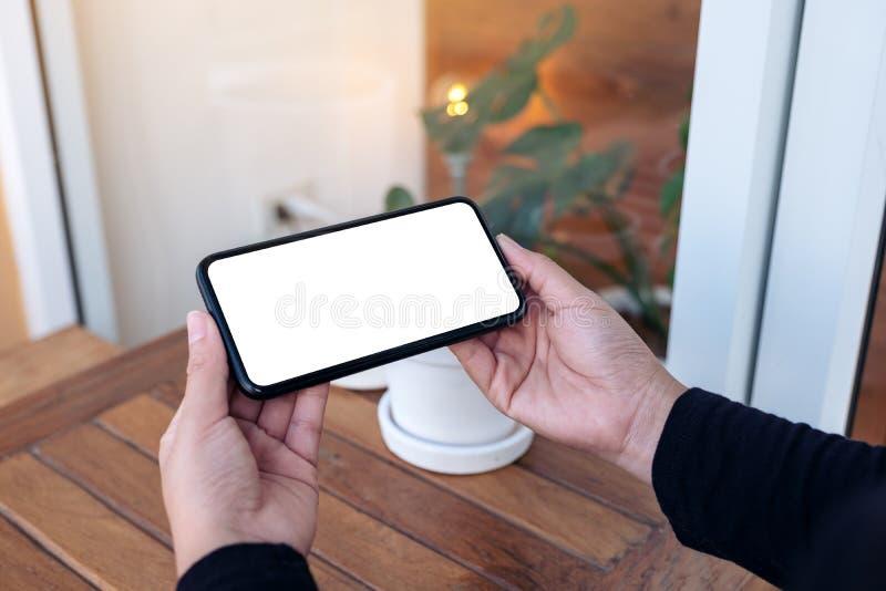 拿着和使用有水平黑屏的手一个黑手机为观看在户外 库存照片