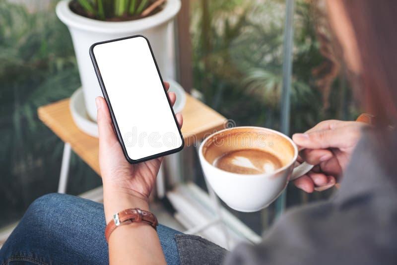 拿着和使用有空白的桌面屏幕的妇女黑手机,当喝咖啡在咖啡馆时 免版税图库摄影