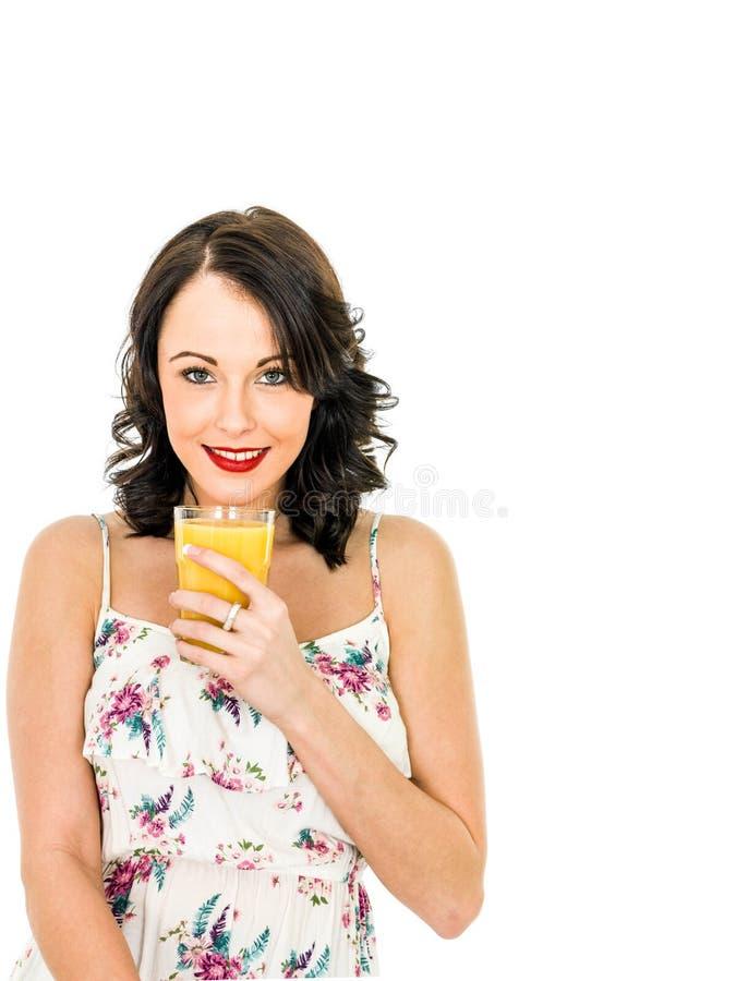 拿着和喝一杯新鲜的健康桔子的少妇 库存图片