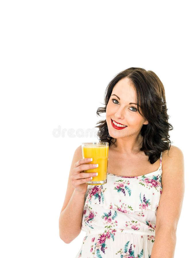 拿着和喝一杯新鲜的健康桔子的少妇 免版税库存图片