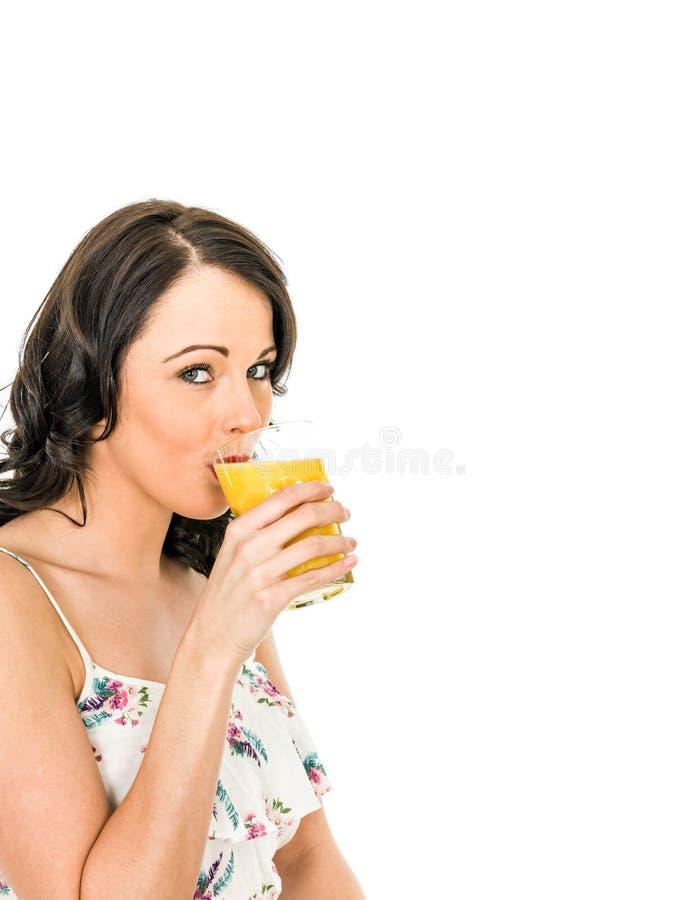 拿着和喝一杯新鲜的健康桔子的少妇 免版税图库摄影