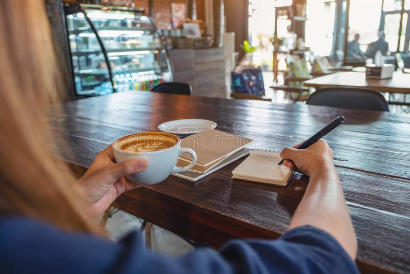 拿着和喝热的咖啡的妇女,当写在木桌上的笔记本在咖啡馆时 图库摄影