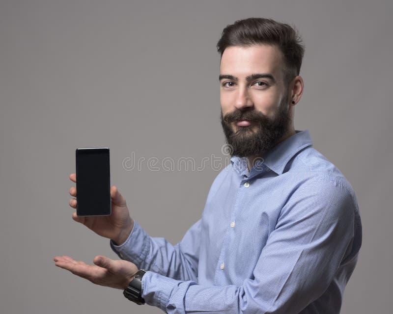拿着和当前空白的聪明的电话设备显示的年轻有胡子的微笑的正面商人 图库摄影