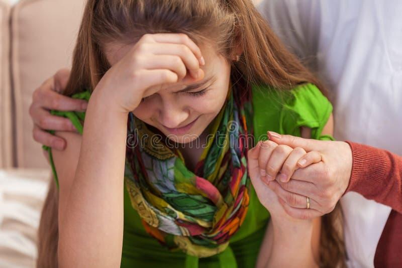 拿着和慰问哭泣的少女的妇女手 少年问题概念,关闭  免版税库存图片