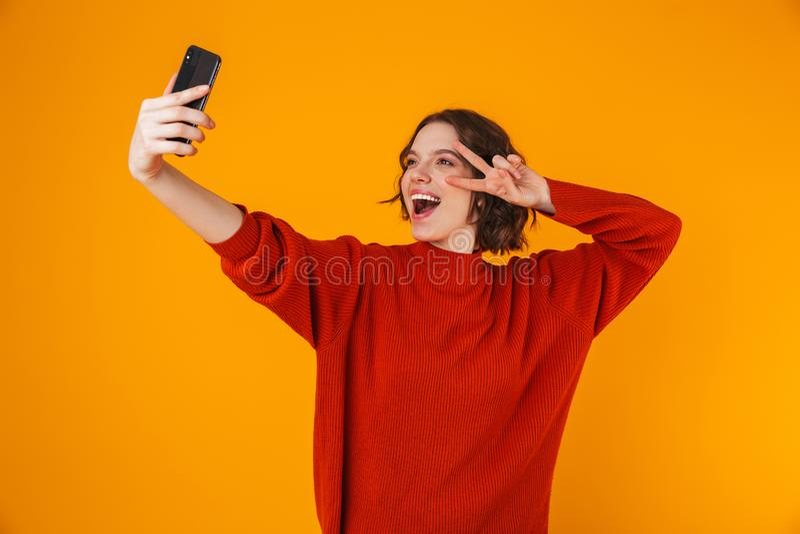 拿着和拍在手机的欢悦妇女画象selfie照片,当站立隔绝在黄色背景时 免版税库存照片
