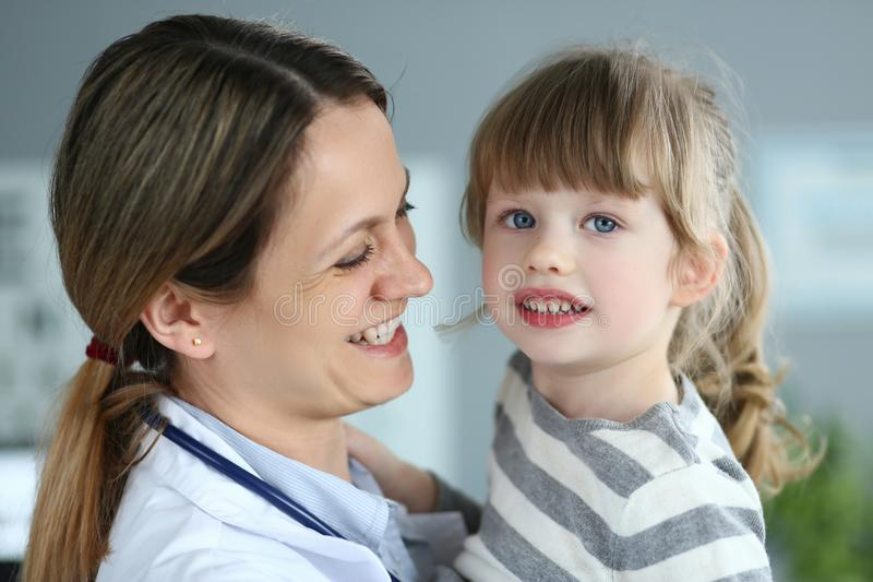 拿着和拥抱一点逗人喜爱的女孩患者的小儿科医生 免版税库存图片
