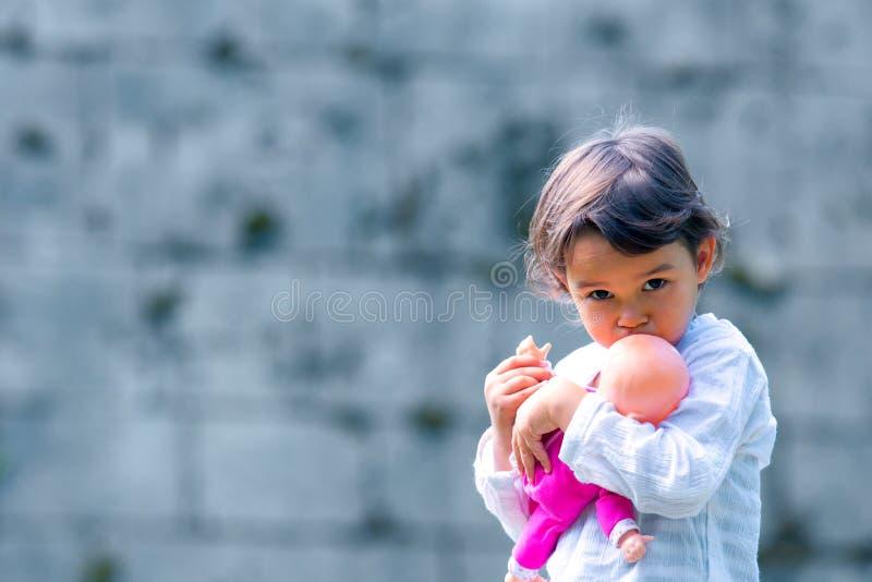 拿着和拥抱她的玩偶的逗人喜爱的小女孩 库存图片