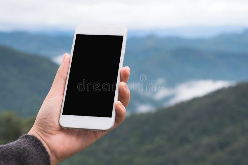 拿着和显示有空白的桌面屏幕的手白色巧妙的电话在室外有迷离绿色山背景 免版税库存图片