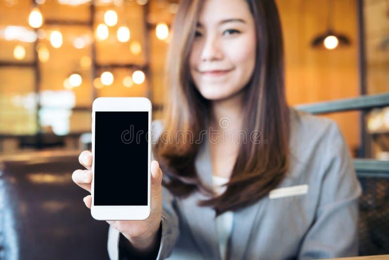 拿着和显示有空白的黑屏幕和面带笑容面孔的亚裔美丽的女商人白色手机在咖啡馆 免版税库存图片