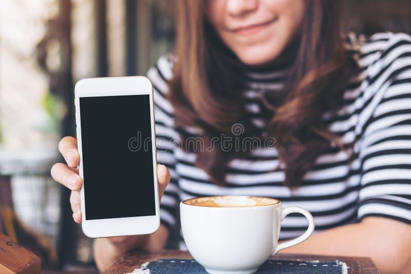拿着和显示有空白的黑屏幕的一名美丽的妇女的大模型图象白色手机有兴高采烈的面孔和咖啡杯的o 库存图片