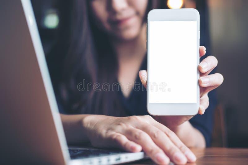 拿着和显示有黑屏幕的一名兴高采烈的亚裔美丽的妇女的大模型图象白色手机,当使用在木头时的膝上型计算机 库存图片
