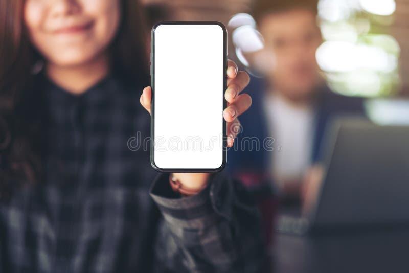 拿着和显示有黑屏的妇女黑手机有工作的商人的在背景中 库存图片