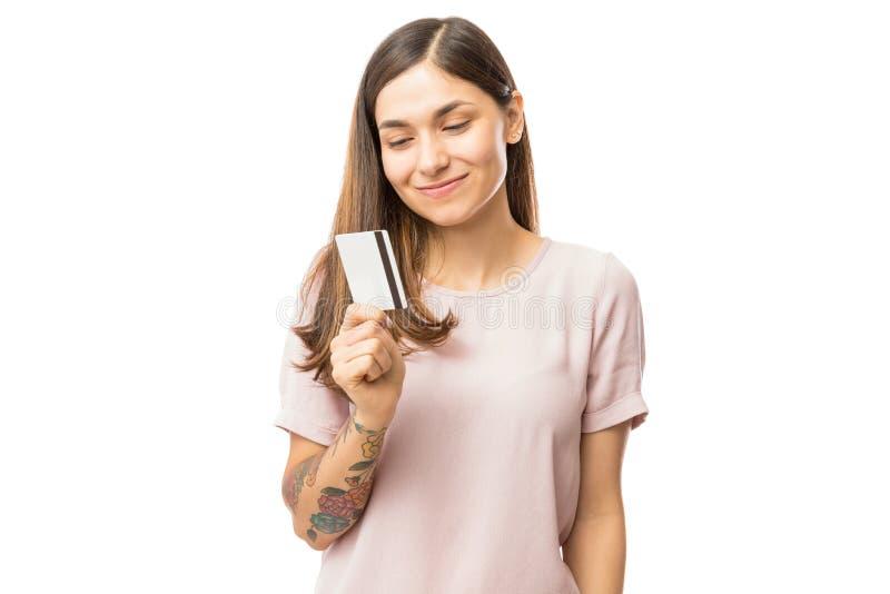 拿着和看信用卡的微笑的少妇 图库摄影