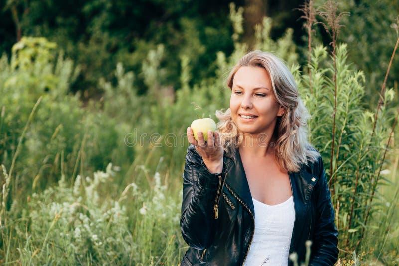 拿着和看绿色苹果计算机的妇女,当放松在公园时 免版税图库摄影