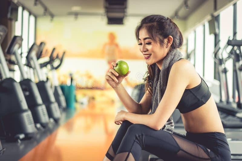 拿着和看起来绿色苹果的亚裔妇女吃用运动器材和踏车在背景中 干净食物和健康 免版税库存图片