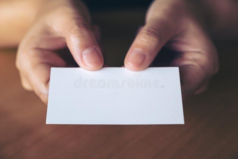 拿着和给一张空的名片的手某人在桌上在办公室 免版税图库摄影