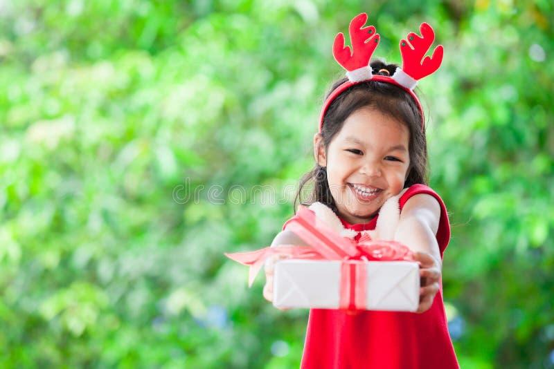 拿着和给圣诞节礼物的逗人喜爱的亚裔儿童女孩 库存照片