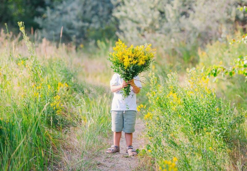 拿着和给黄色野花的花束逗人喜爱的小男孩掩藏他的在它后的面孔 免版税库存照片