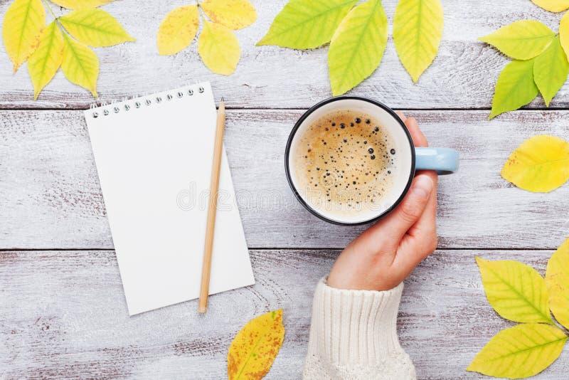 拿着咖啡、开放笔记本和秋叶的妇女手在葡萄酒木台式视图 舒适早餐 免版税库存照片