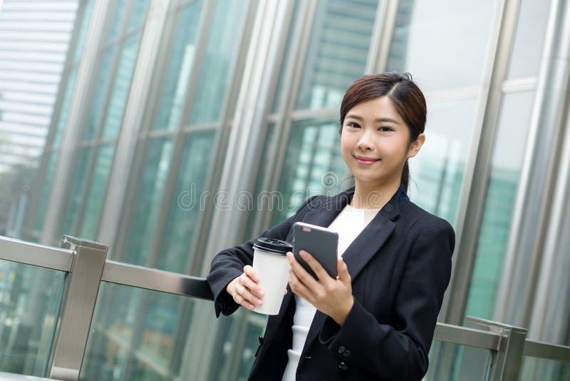 拿着咖啡和她的手机在办公室外的女商人 免版税库存照片