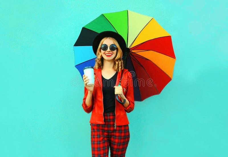 拿着咖啡杯和五颜六色的伞在红色夹克,黑帽会议的画象微笑的年轻女人在蓝色墙壁上 库存图片