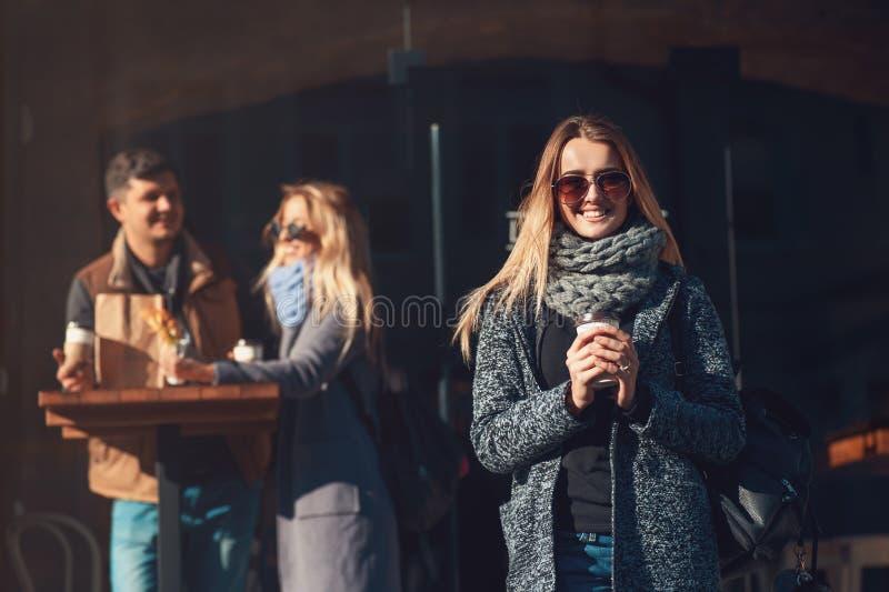 拿着咖啡杯和新月形面包和看与微笑的太阳镜的美丽的年轻白肤金发的妇女照相机 免版税图库摄影