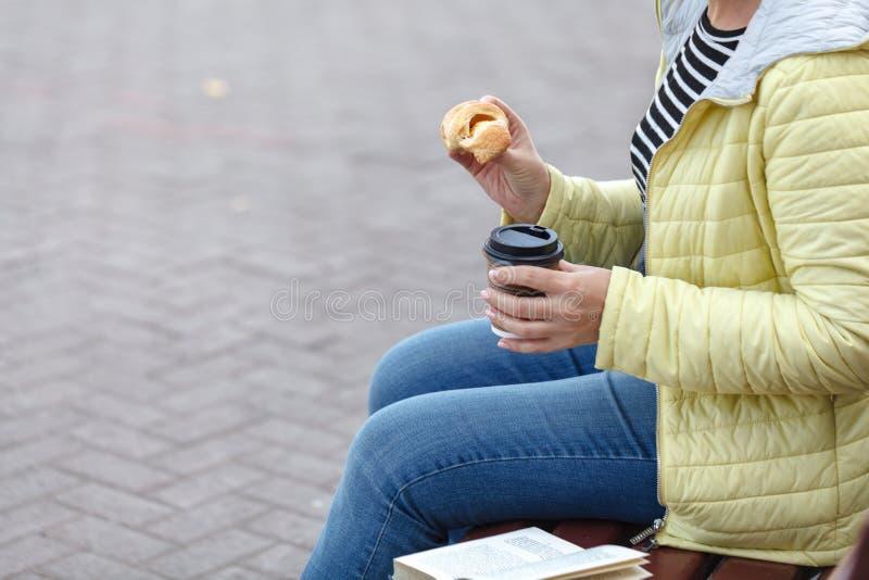 拿着咖啡杯和新月形面包的美丽的妇女 库存照片