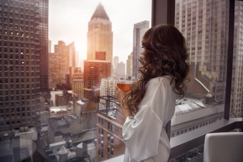 拿着咖啡杯和看对在豪华曼哈顿顶楼房屋公寓的窗口的美丽的妇女 免版税库存照片