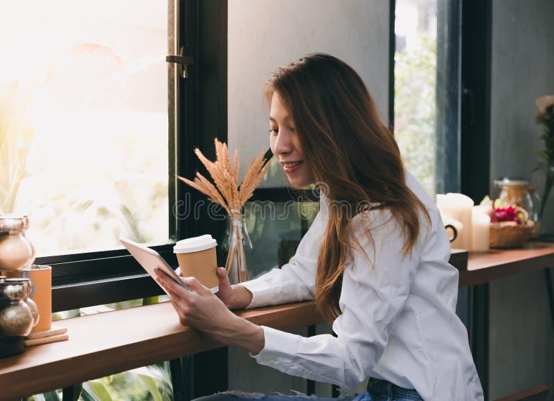 拿着咖啡杯和读报告的亚裔女实业家在选项 免版税库存图片