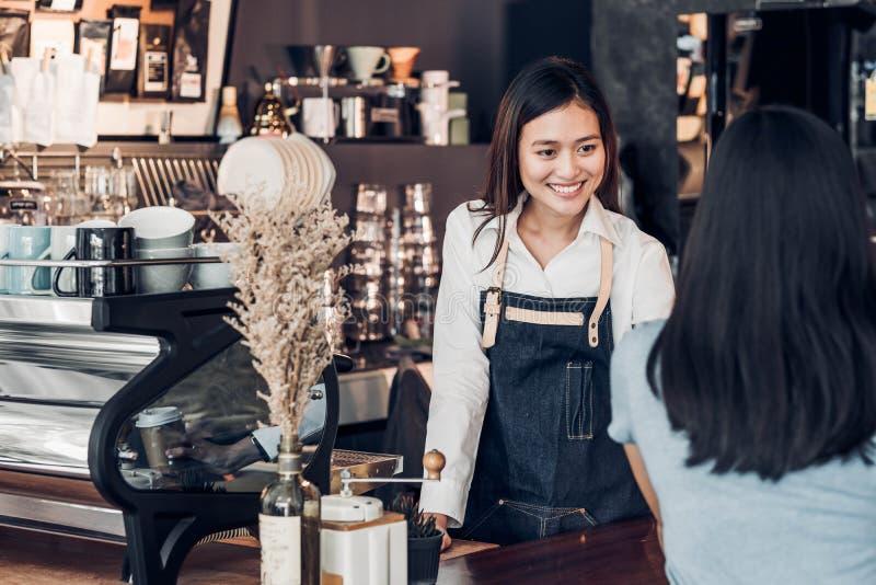 拿着咖啡杯的亚洲妇女barista穿戴斜纹布围裙服务给顾客在酒吧柜台激动微笑,咖啡馆餐馆 库存照片