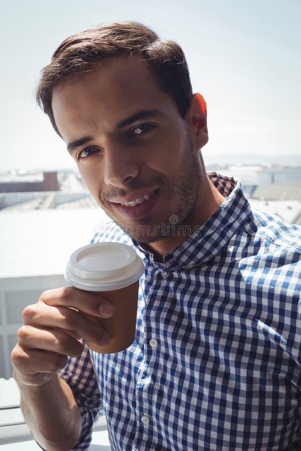 拿着咖啡杯的周道的年轻商人由窗口在办公室 库存照片